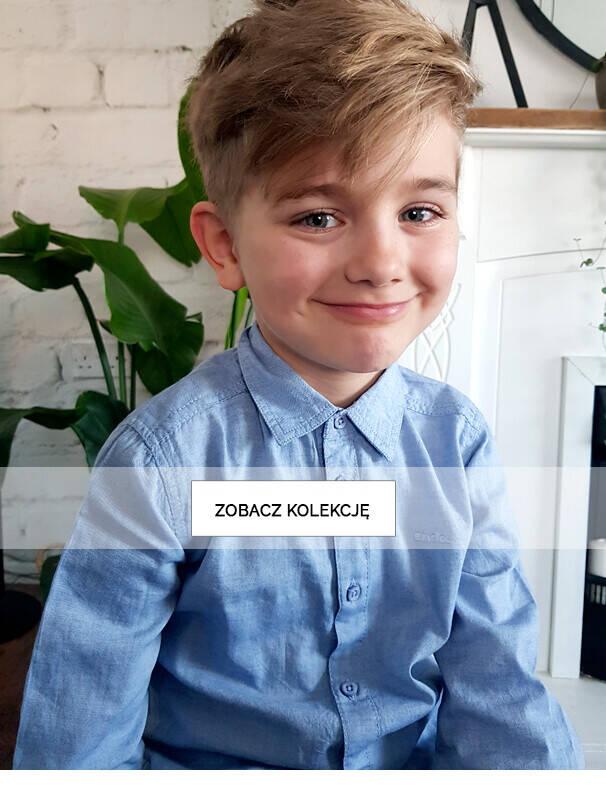 Chłopiec w błękitnej koszuli gotowy na pierwszy dzień szkoły.