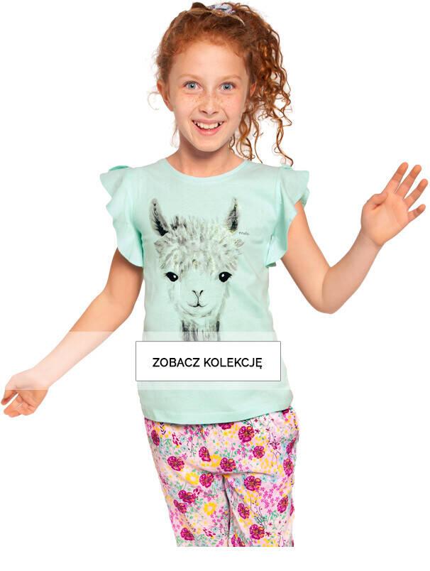 Dziewczynka w miętowej bluzce z lamą i w kolorowych spodniach.