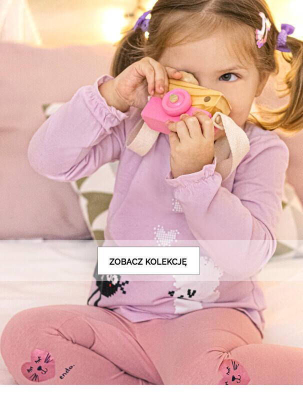 Baner z małą dziewczynką w różowych legginsach.