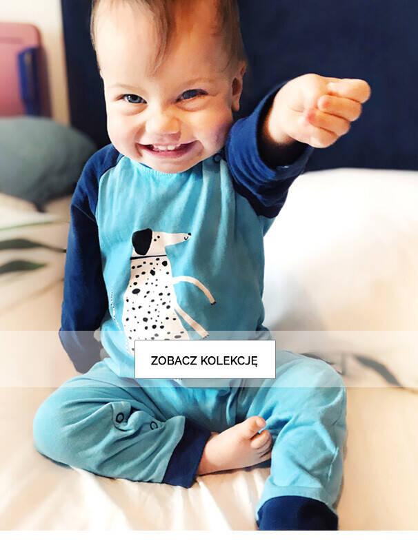 Baner z małym dzieckiem w niebieskim pajacu.