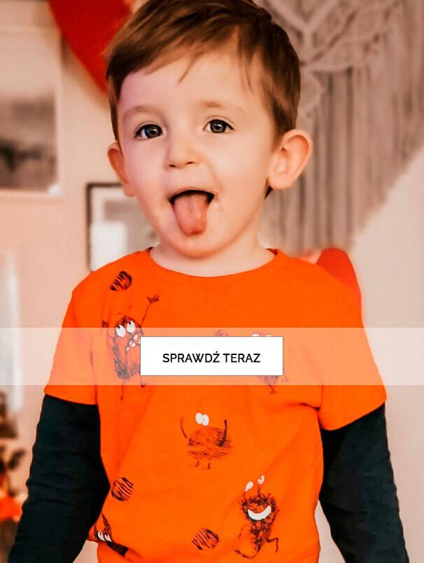 Mały chłopiec w pomarańczowej koszulce pokazujący język.