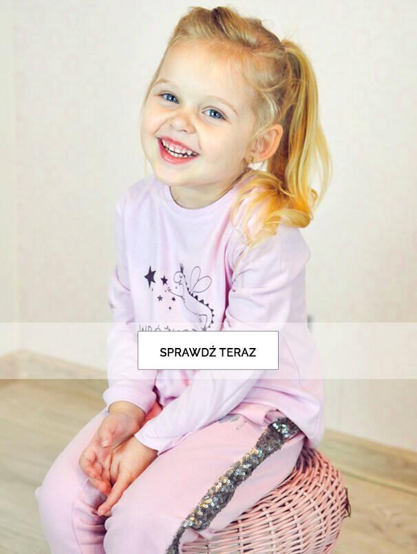 Baner z dziewczynką w różowych spodniach.