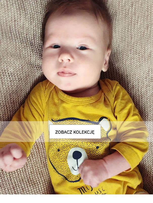 Baner z niemowlęciem w żółtym body.