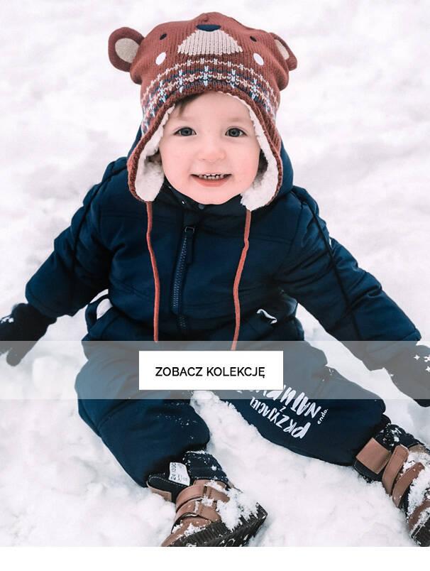 Baner z dzieckiem w zimowym kombinezonie na śniegu.
