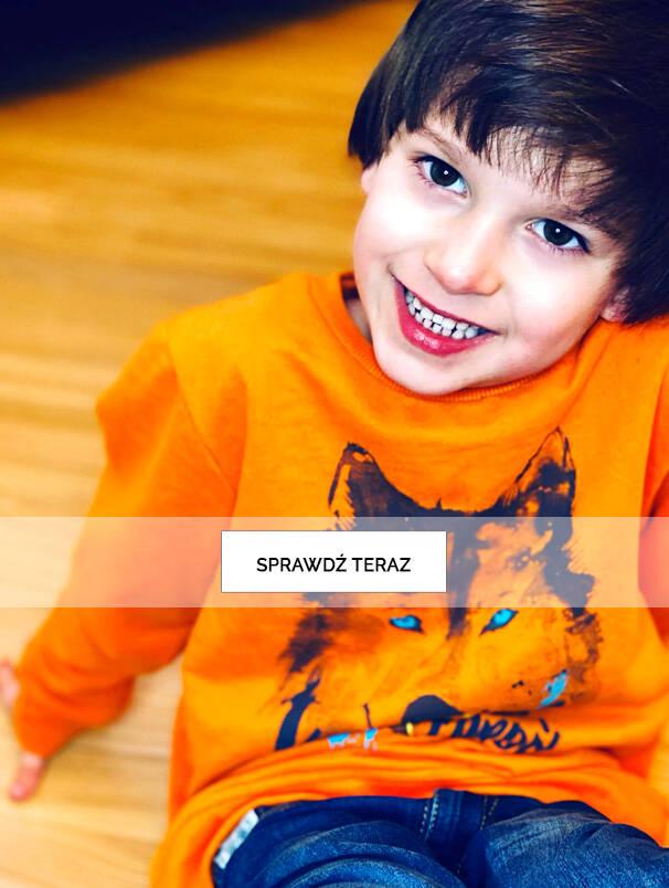 Baner z chłopcem w pomarańczowej koszulce.