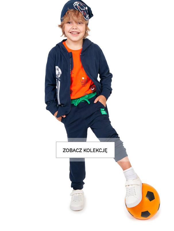 Baner z chłopcem w granatowych spodniach dresowych.
