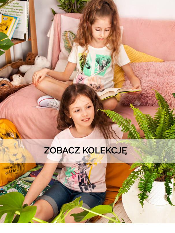 Baner z dziewczynkami w kolorowych koszulkach.