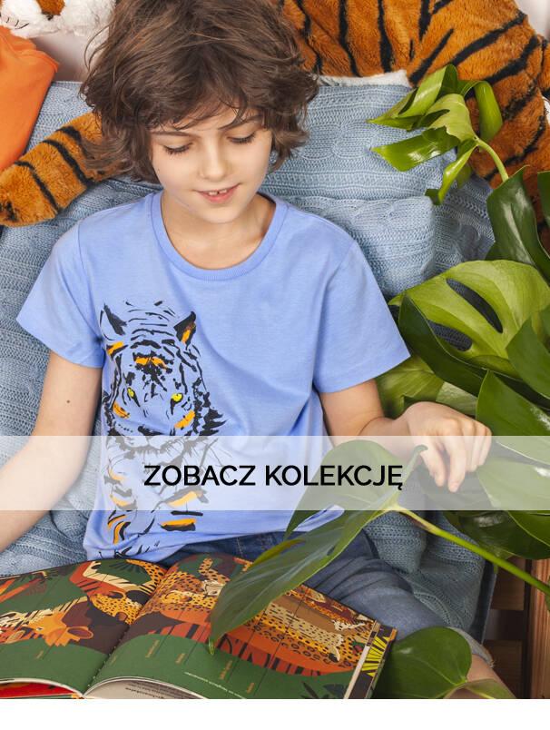 Baner z chłopcem w niebieskiej koszulce z krótkim rękawem.